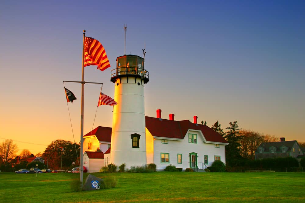 things to do on cape cod header image - photo of classic new england lighthouse with sunsetting behind, Chatham Lighthouse, Massachusetts. american flag is next to the white lighthouse