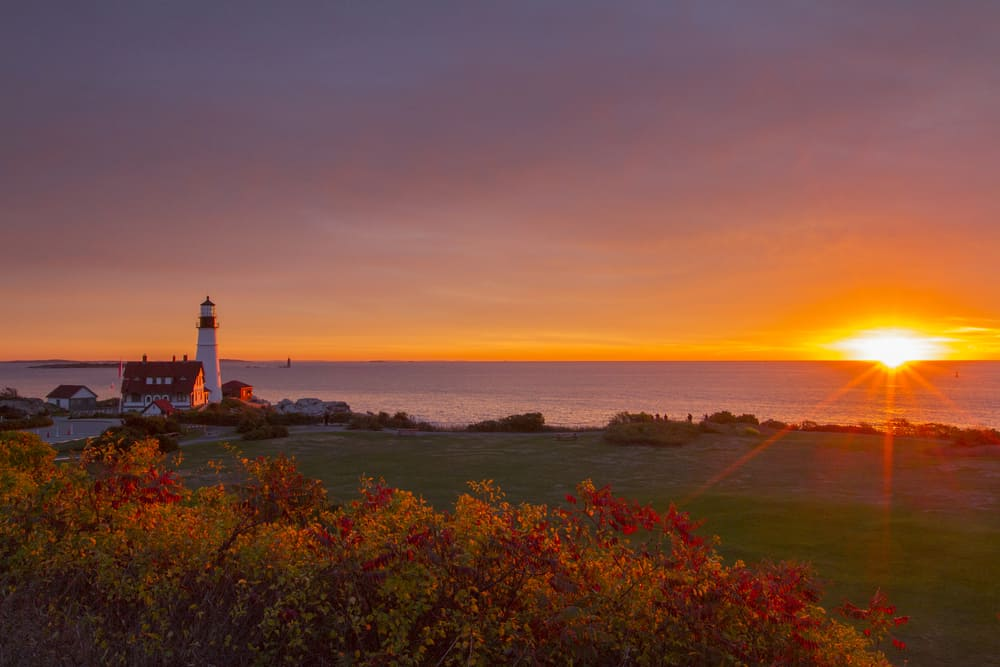 places to visit in maine - image of spectacular purple-hued sunrise over Portland Head Light lighthouse in Portland ME