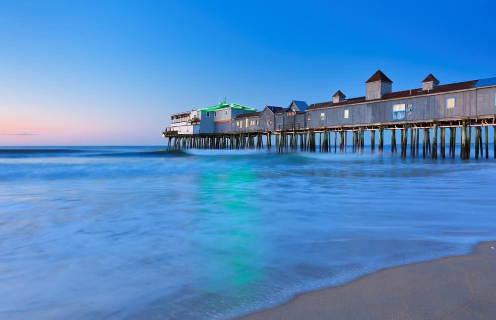 calm blue ocean water reflects the light of a long beachside pier at sunset