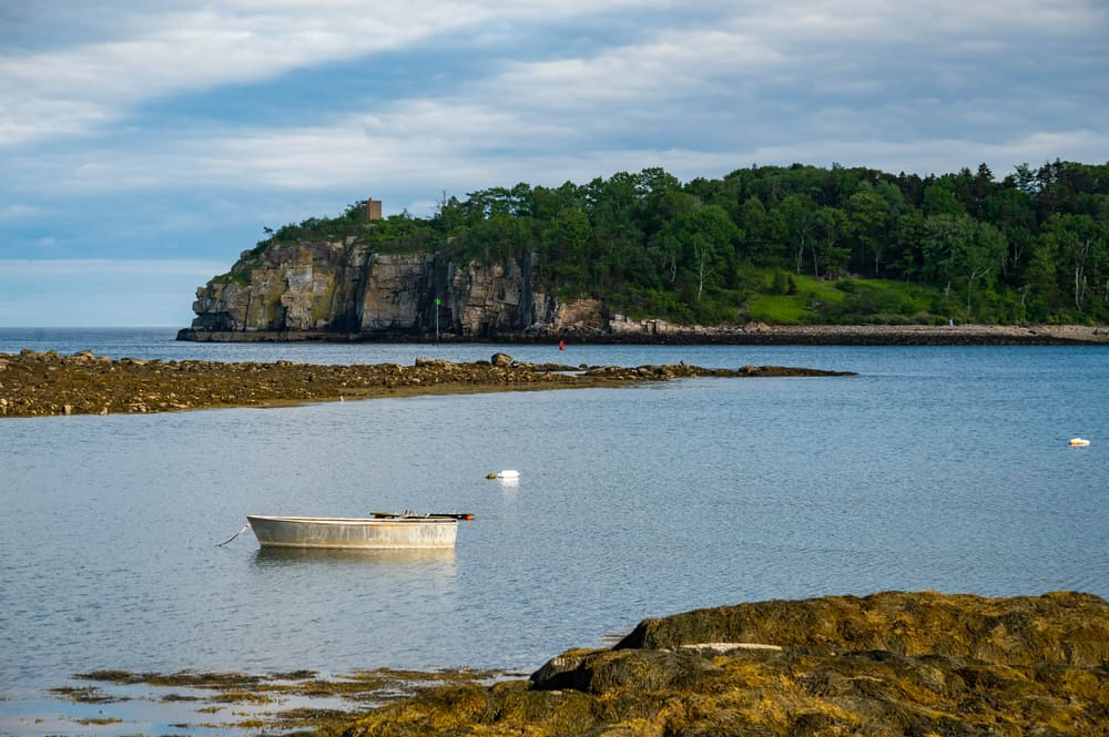 a lone small white boat moored in front of a rocky island, maine