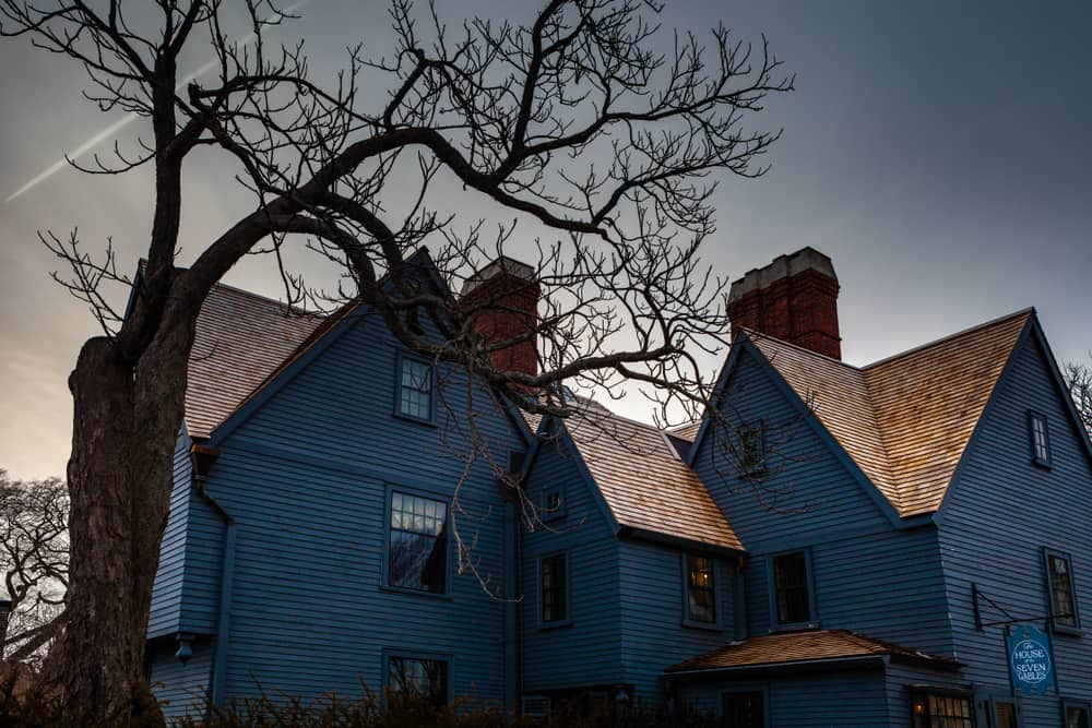dark image of creepy colonial house behind bare, ominous tree - haunted places in salem ma