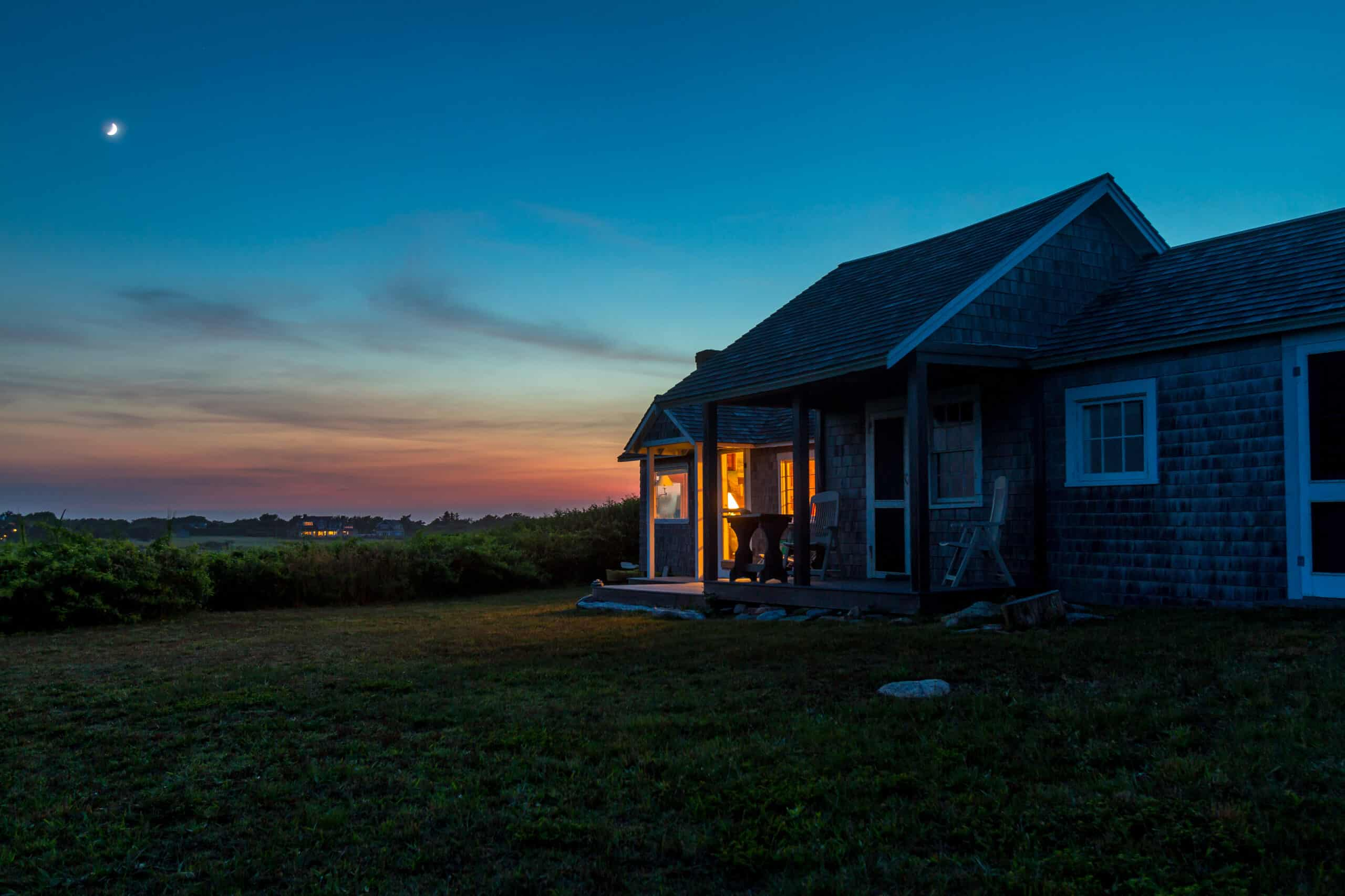 airbnb provincetown ma - classic new england cottage during a dark sunset on the coast