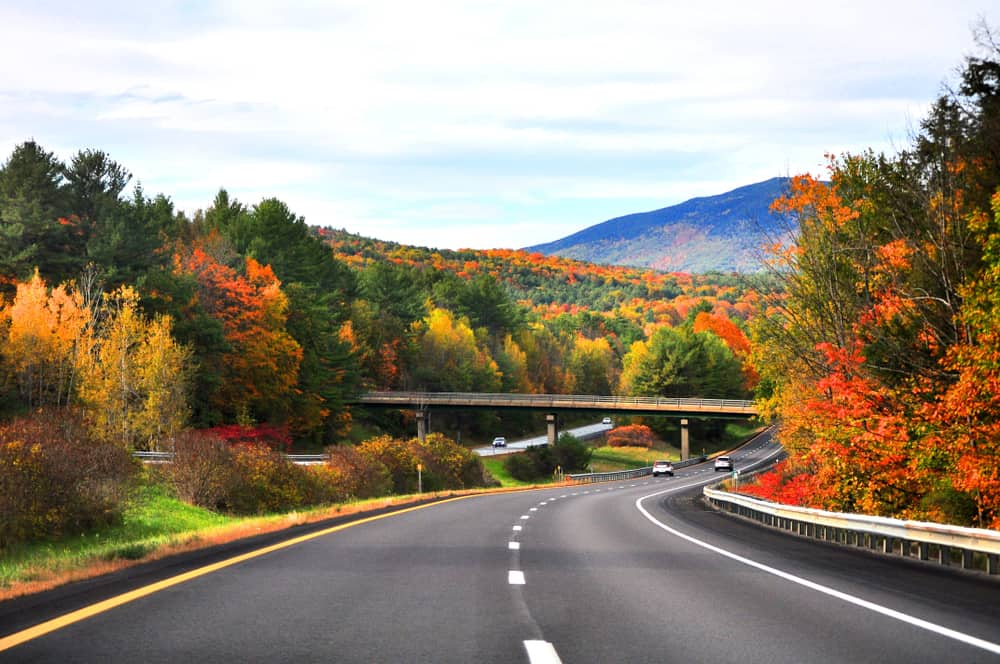 a vermont road trip - an empty road stretching into the distant mountains, fall foliage lines the highway