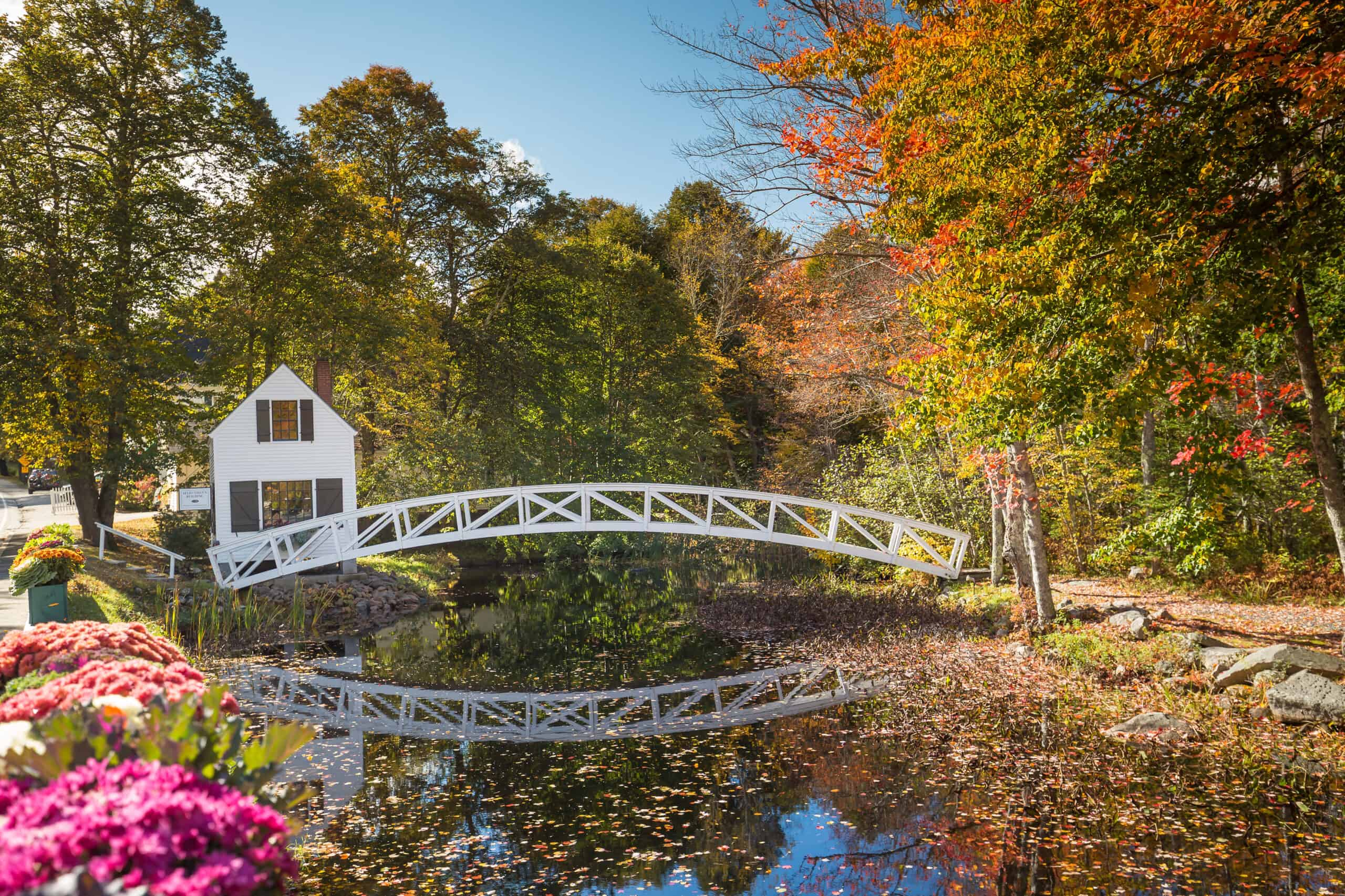 best airbnbs in acadia and bar harbor maine - image of delicate white bridge spanning pond surrounded by fall trees