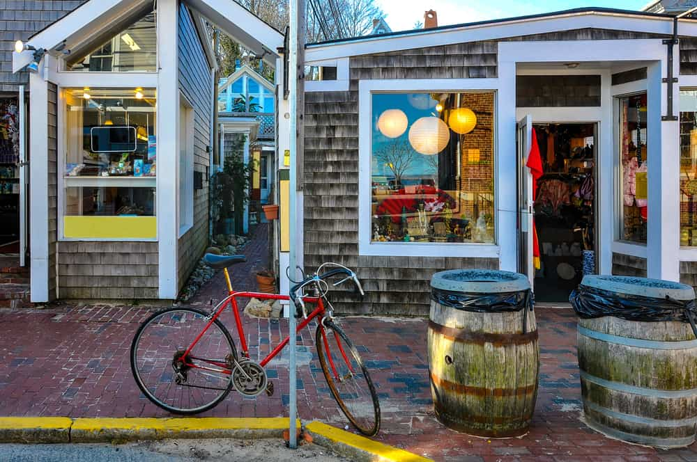 things to do in provincetown ma - image of red bicycle parked in front of cozy new england style shop