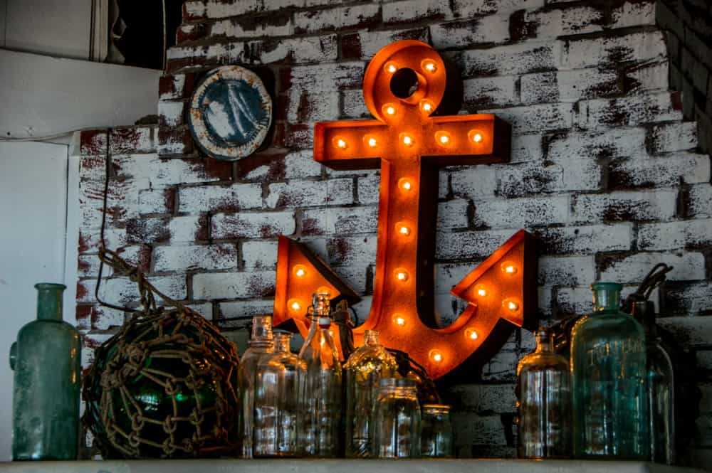airbnb portland maine - image of grey brick wall with an illuminated orange anchor decoration