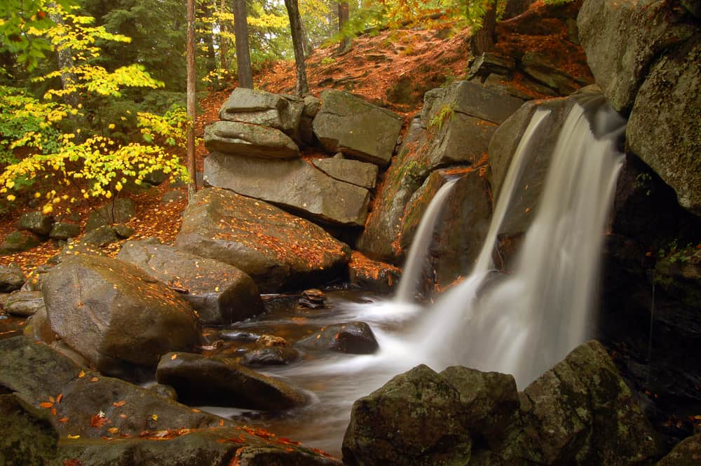 waterfalls in massachusetts - image of small waterfall falling over grey rocks covered in fall leaves