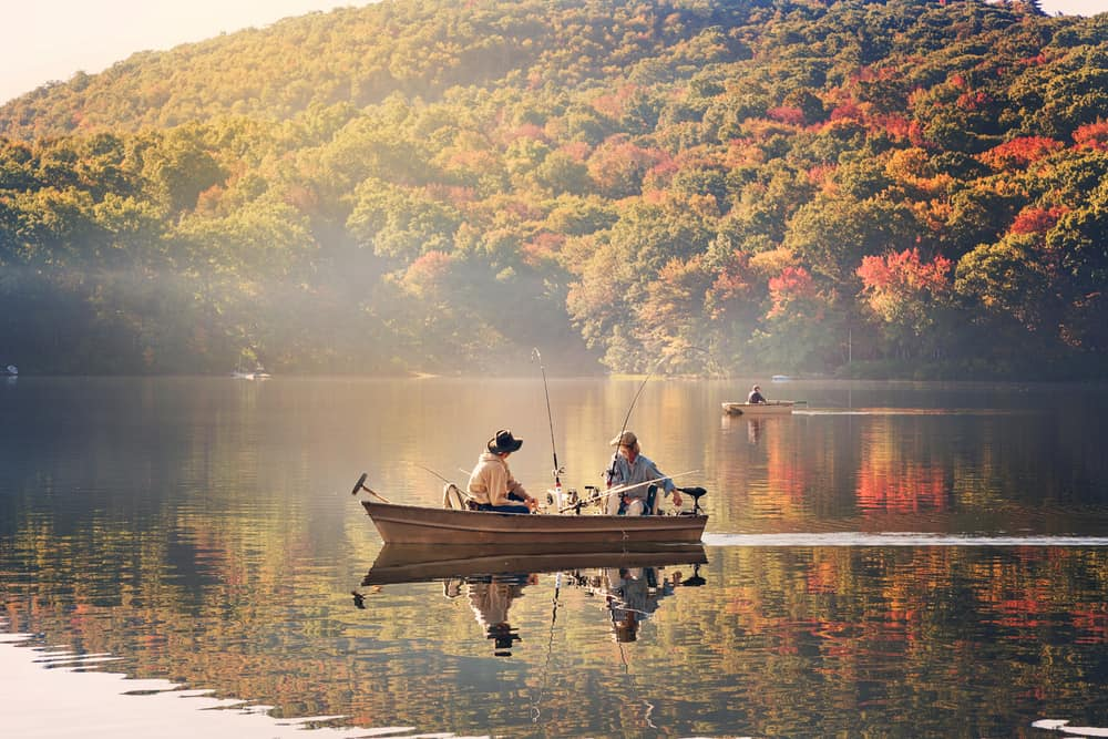 two people fishing in a small boat on a lake surrounded by fall foliage - things to do in northampton ma