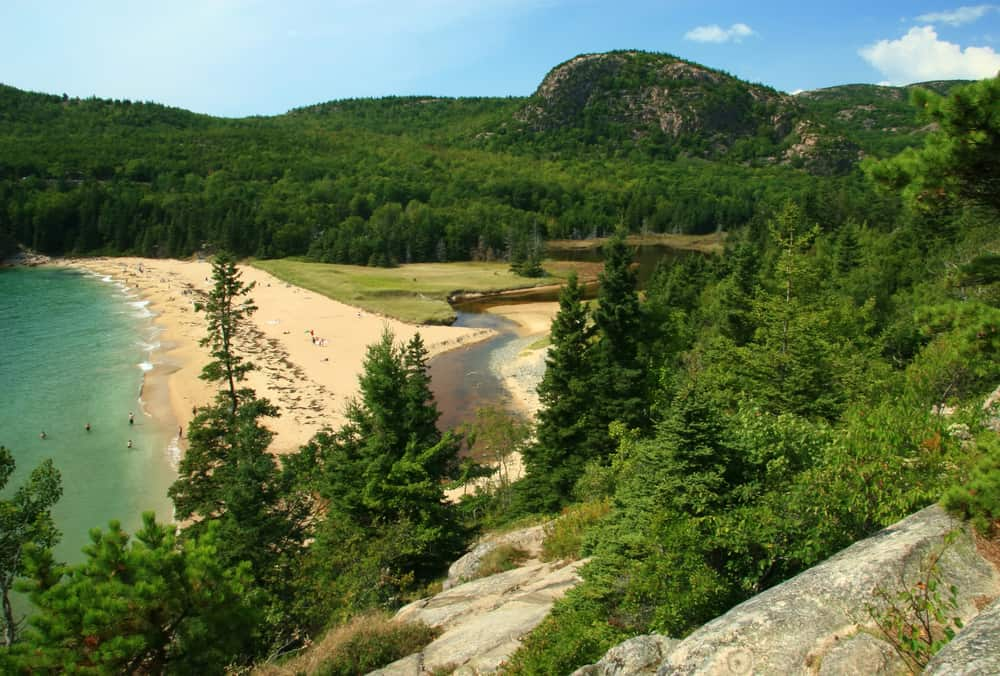 best beaches in maine - aerial image of a sandy white beach surrounded by deep green trees and mountain in distance
