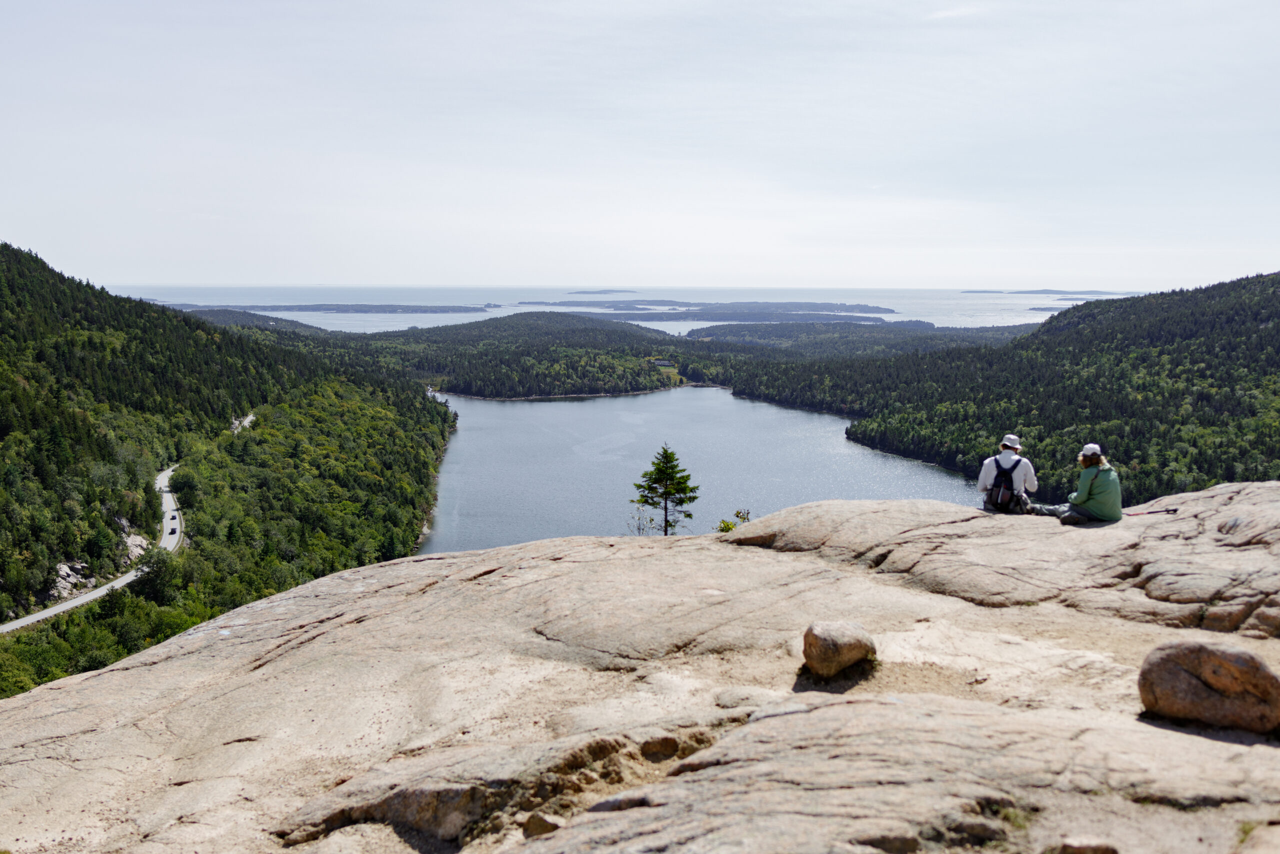 best hikes in acadia national park - two people sit on the end of a large rock overlooking green mountains and a still lake