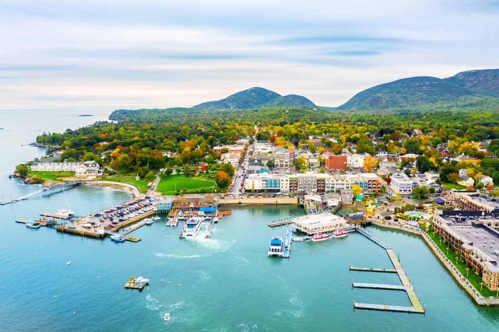 things to do in bar harbor maine - image of small coastal town from above, the turquoise water is seen and green mountains in the distance