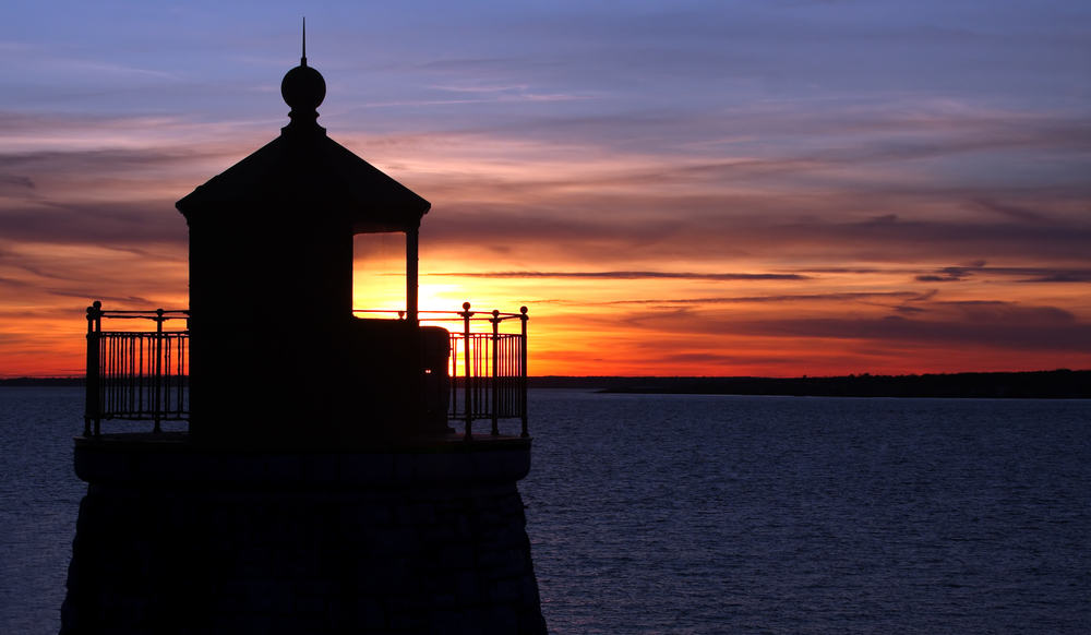 things to do in rhode island - silhouette of lighthouse with a colorful sunset sky in the background and horizon of the ocean