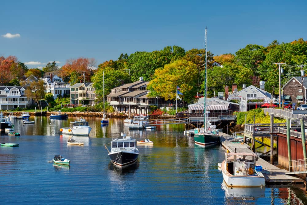 one of the coastal small towns in maine as seen from the harbor - boats in front of quaint houses