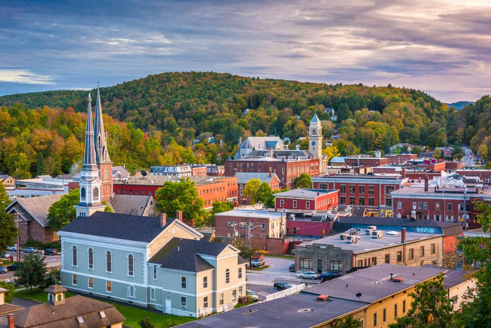 things to do in montpelier vt - image of small Vermont city skyline at sunset, low green hills in background