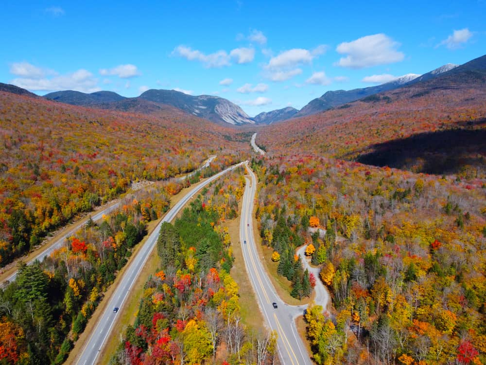 things to do in the white mountains - drone image of new hampshire fall foliage surrounding scenic highway with mountains in distance