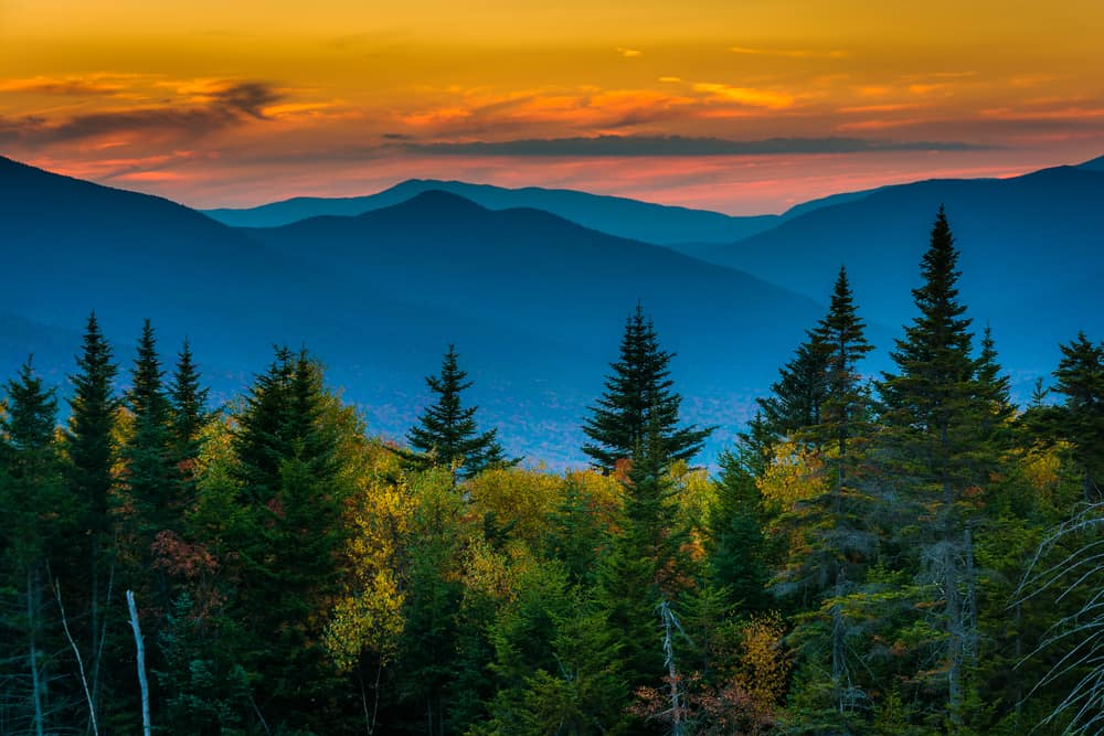 best things to do in new hampshire - colorful image of an orange sunset over bright blue tinged mountains with evergreen trees in the foreground