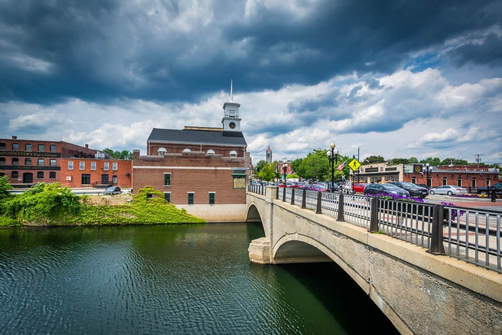 things to do in nashua nh - image of a river and bridge with a classic new england mill town seen across the water
