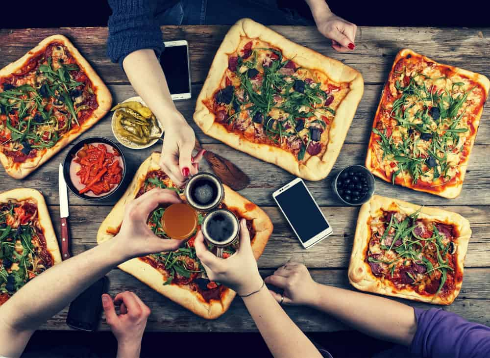 best restaurants in burlington VT - overhead view of friends eating dinner, large spread of pizza and beers are being toasted