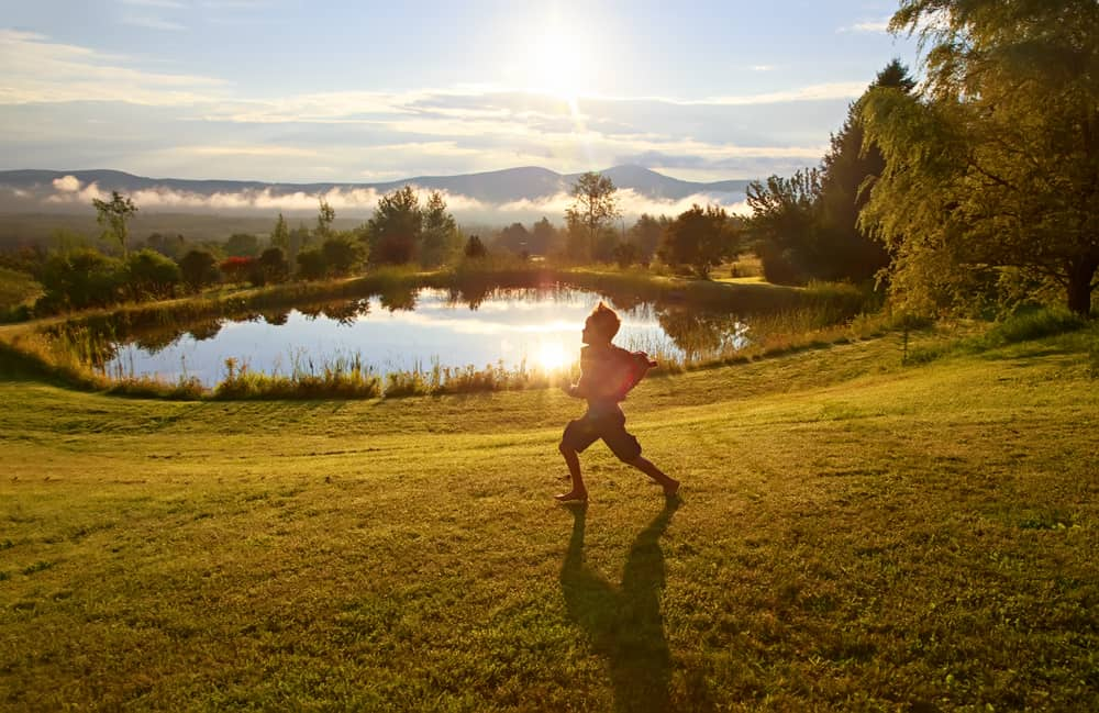 boy running on a golden afternoon in front of a pond -summer in vermont