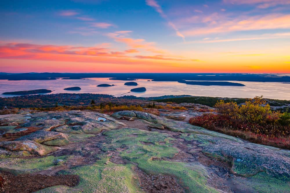 sunset from the top of a mountain overlooking the ocean in maine - most beautiful places in maine cadillac mountain