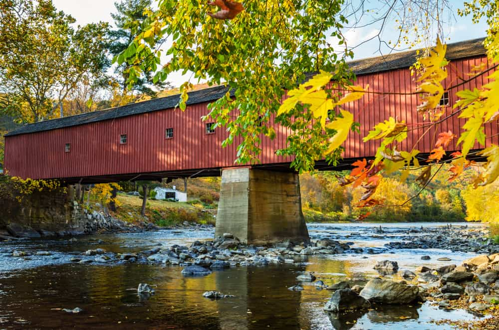 a classic new england image: a red covered bridge spanning a still river in the autumn