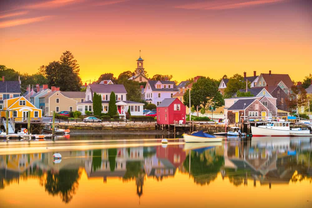 a golden sunrise over the coastal town of portsmouth new hampshire, small houses reflected in the water