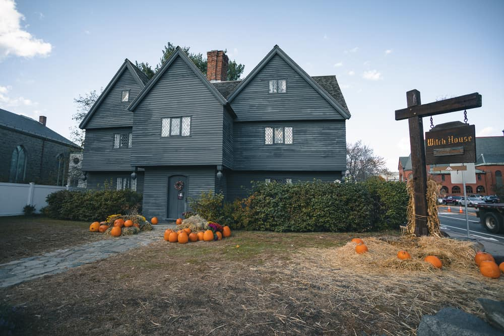 the witch house of salem massachusetts: a dark board house with pumpkins in the front