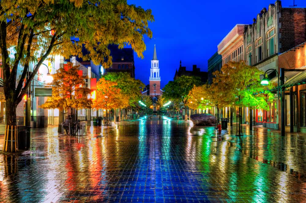 nighttime shot of church street in burlington vermont in the rain - neon colors reflected from small shops in a wet brick road