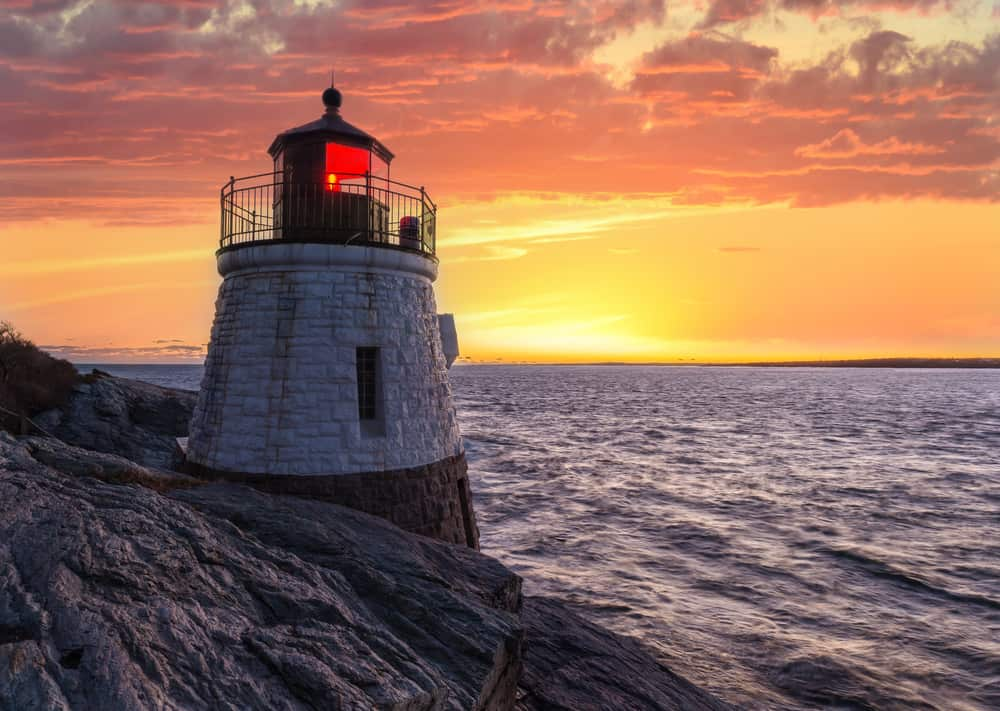 castle hill lighthouse on rocky coast of rhode island near newport, image of small lighthouse with red light in front of ocean and orange sunset