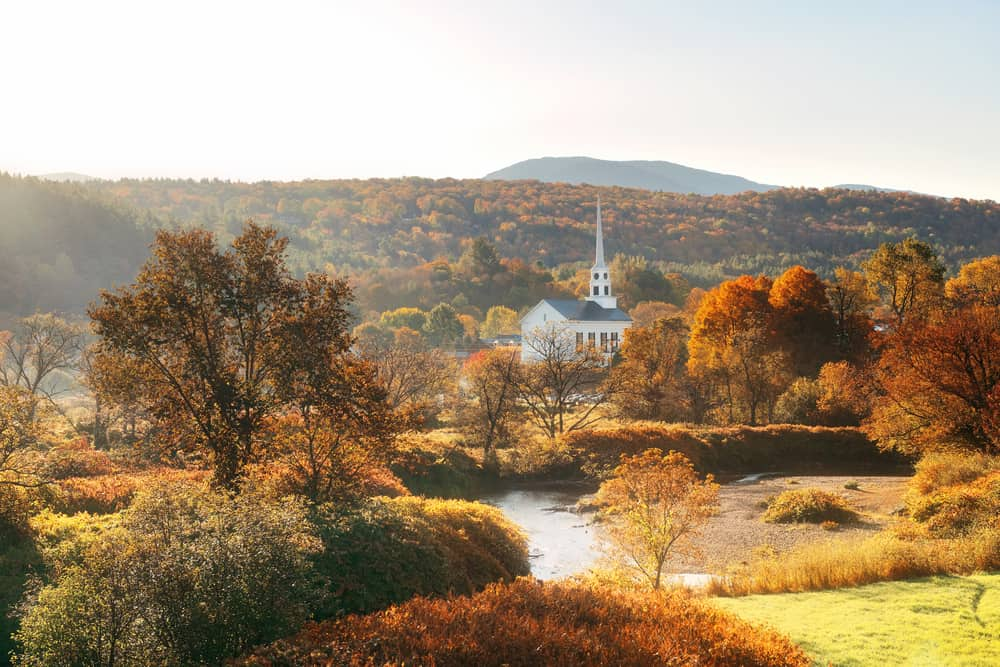 classic new england in the fall: a white church steeple rises above a small town in front of peak autumn foliage