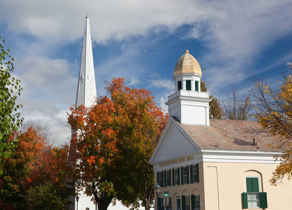 an autumnal tree sits between a gold domed courthouse and a classic vermont white church steeple