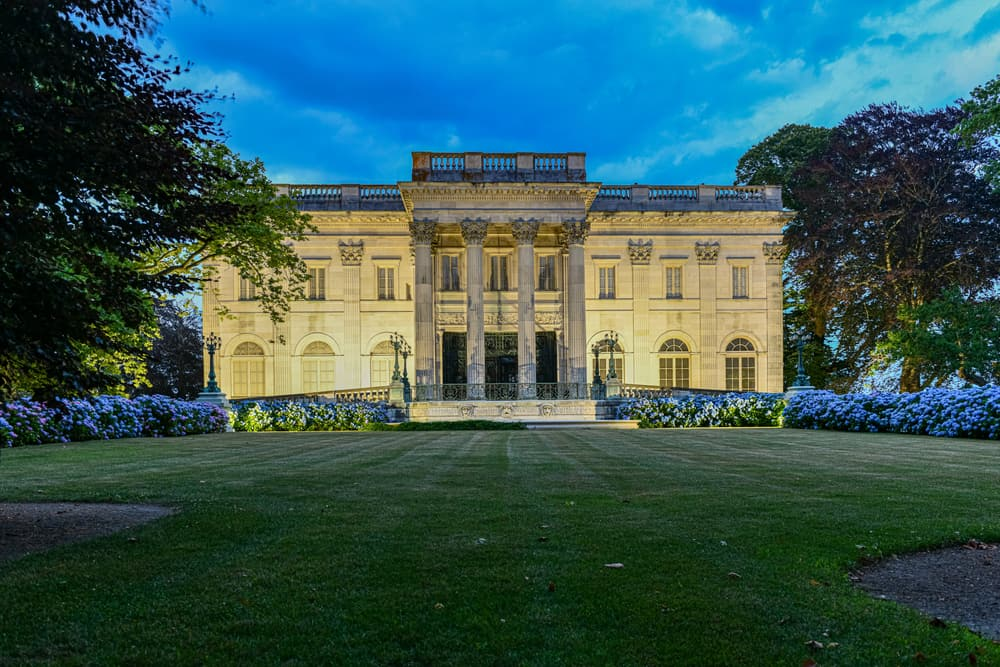 an ivory colored mansion is illuminated at night front the front, a long green lawn lies in front