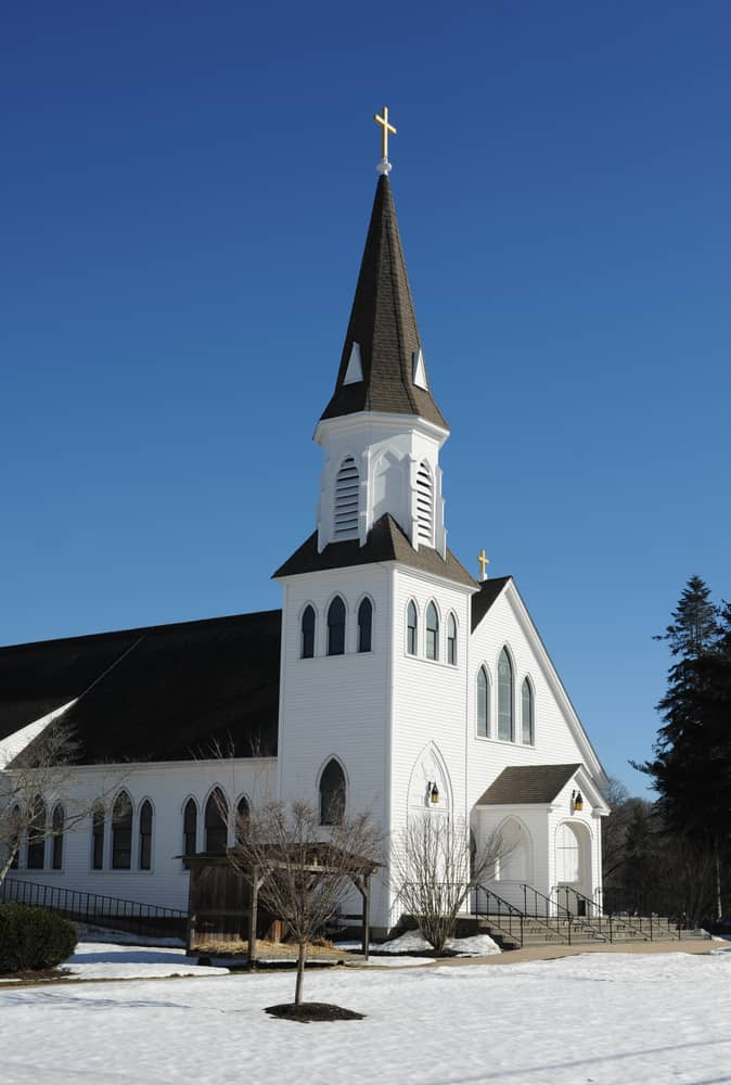 a classic new england white church with a tall steeple and snow on the ground