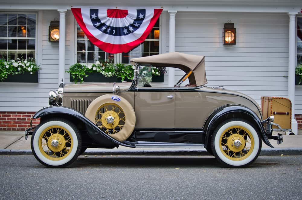 Picture of an antique car in front of a white house with american flag bunting
