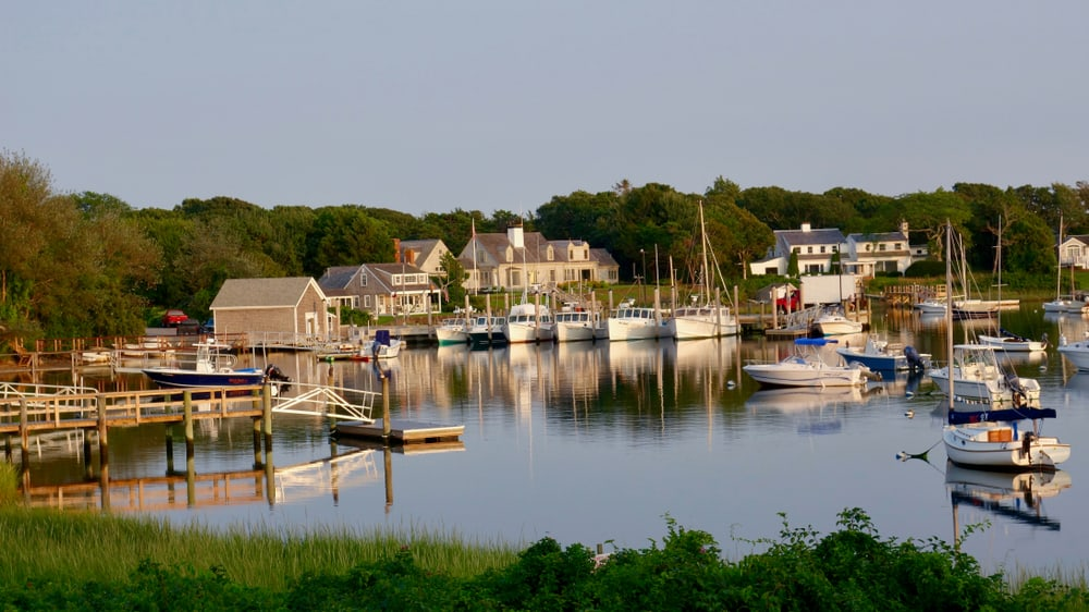 tranquil new england harbor with boats and homes, dusk