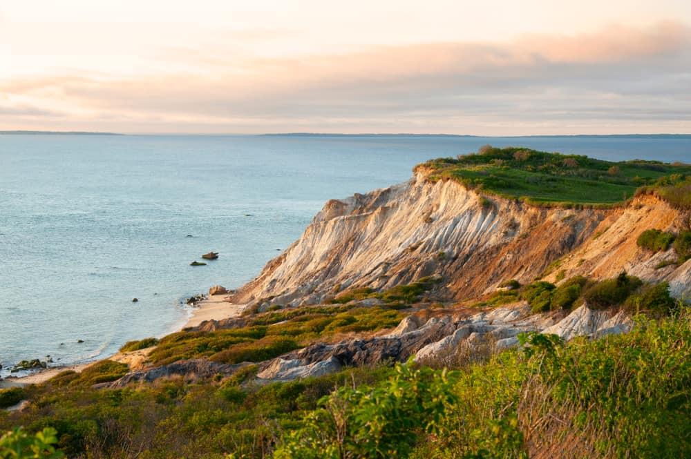 sharp white cliffs with grassy tops next to a still blue ocean