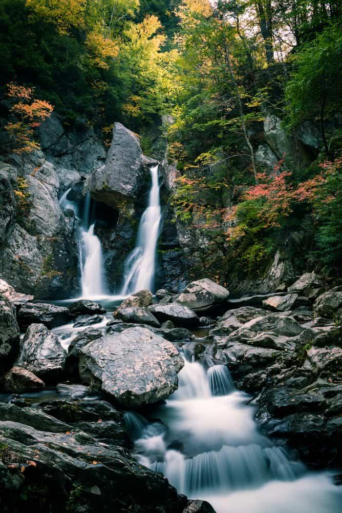 image of a thin and serene waterfall tumbling among deep grey rocks, massachusetts