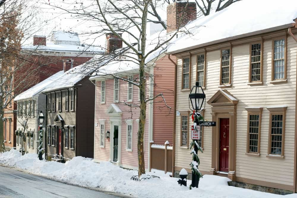 snow is piled in front of classic american colonial homes on a street in rhode island