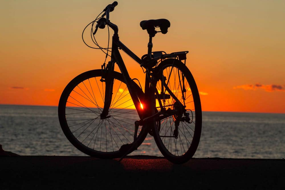 bicycle silhouetted in front of a sunset on the beach