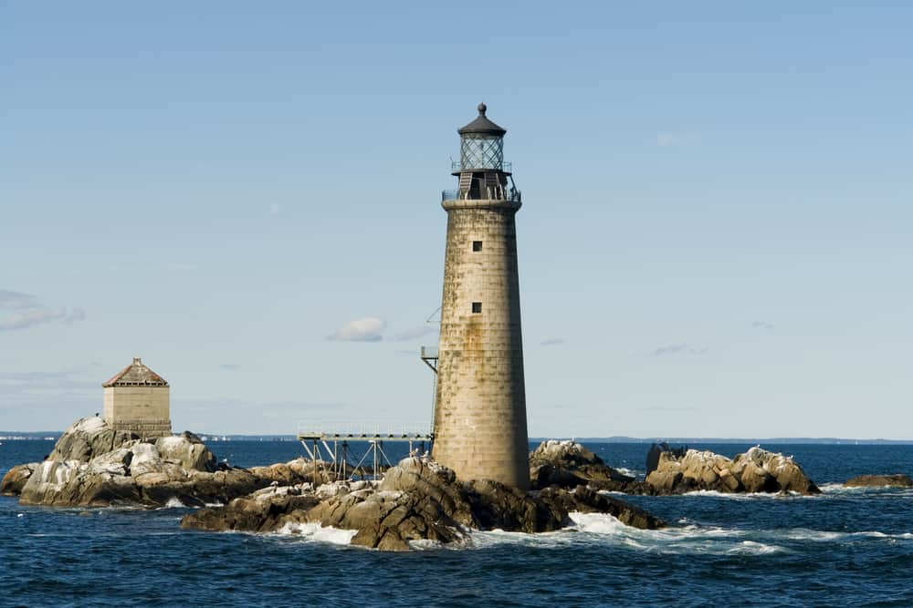 A picture of an old looking lighthouse amidst the sea in Boston Harbor Islands