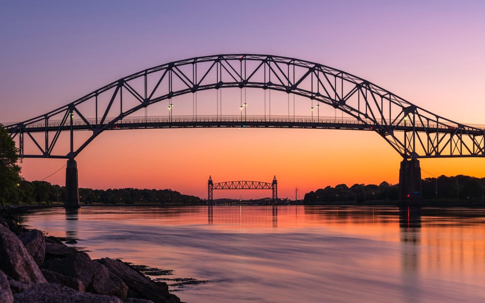 A sunset view of a bridge over the river