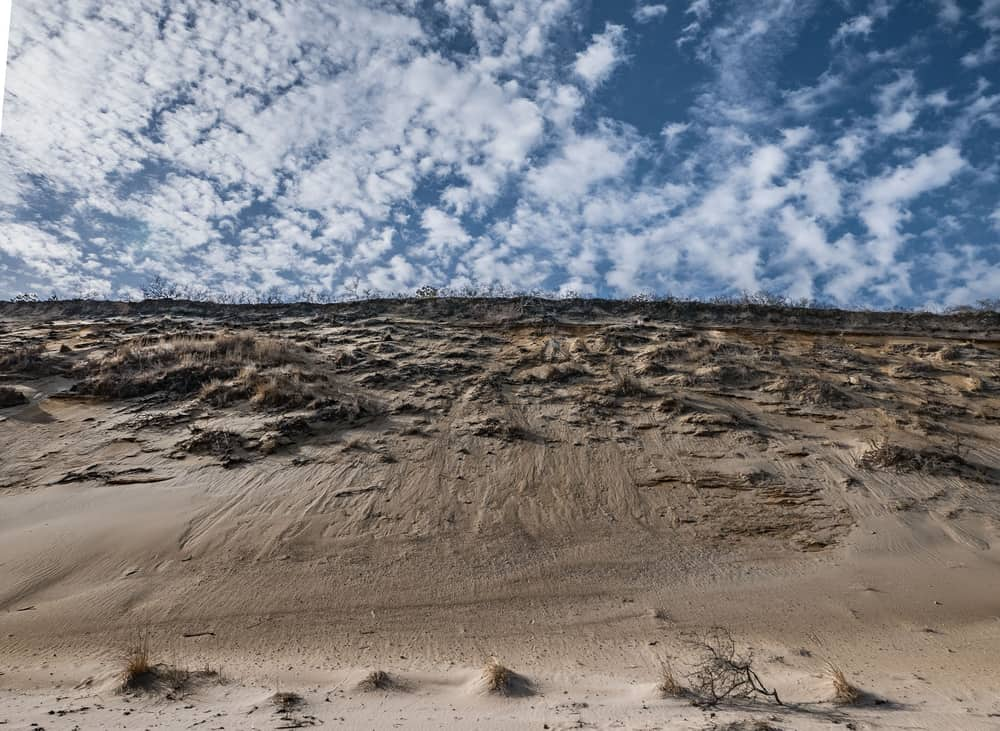 A vast stretch of high Dunes with the blue sky and wispy clouds