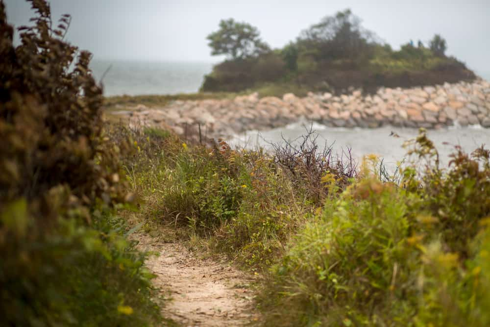 cape cod hikes header - image of a grey day, a narrow sandy path is seen next to a rocky shoreline