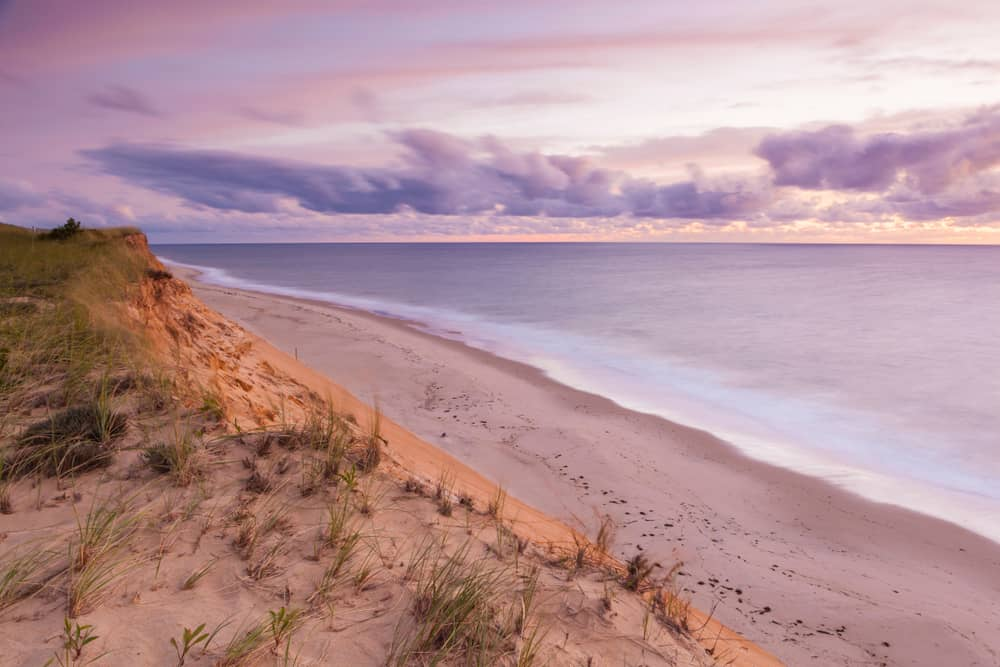 A purple sunset over dunes on the seashore in Cape Cod, one of the most beautiful places in MA