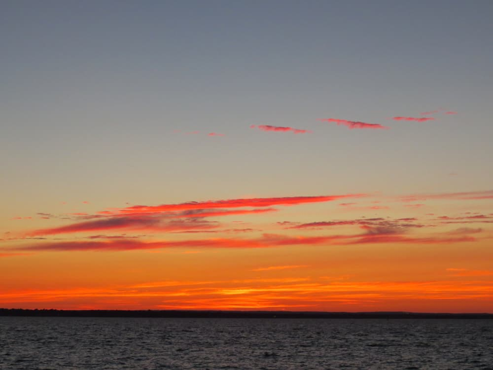 an orange sunset seen over a flat blue/grey sea in new england