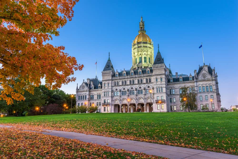 The picture shows the connecticut-capitol illuminated at night, fall leaves in foreground