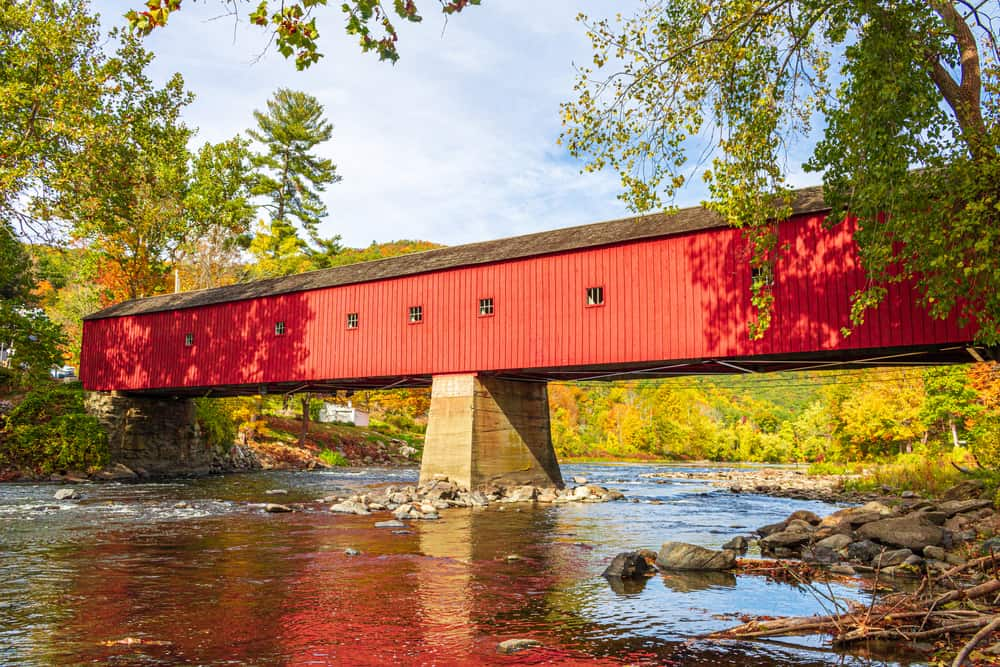 a classic bright red covered bridge in the autumn
