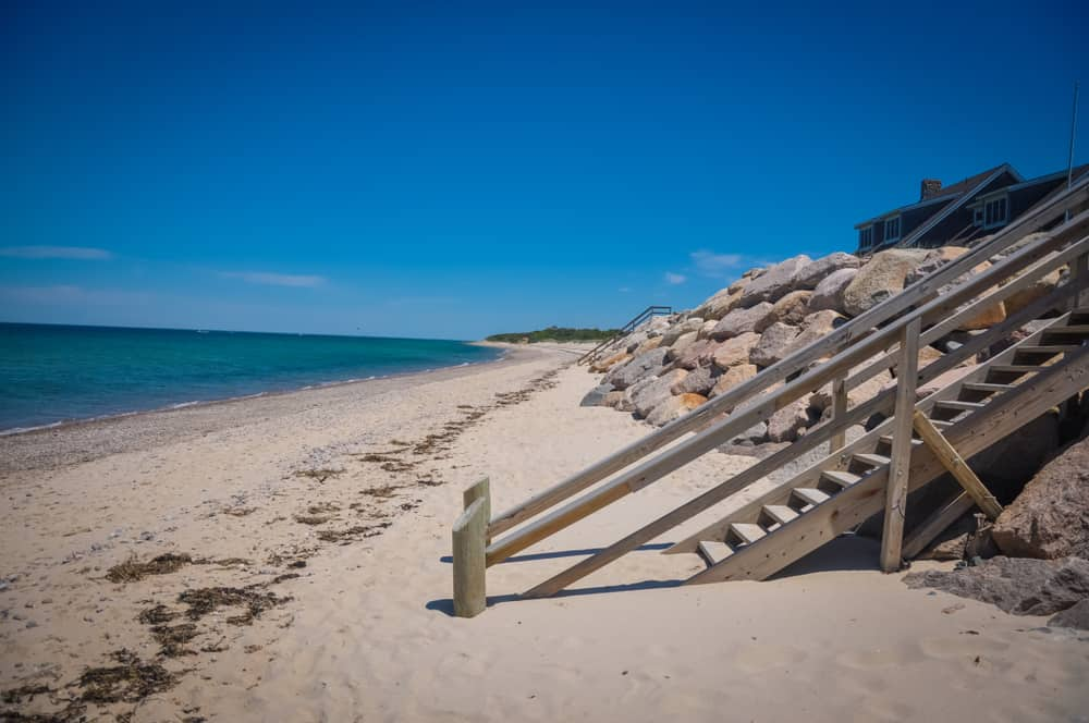 Stairs leading to a white sand beach and the sea in Cape Cod Massachusetts
