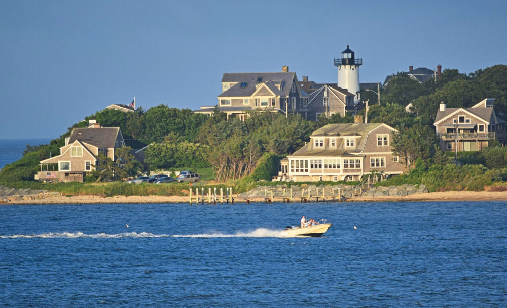 Things to Do in Martha's Vineyard - image of boat on water in front of classic new england town, beige houses with lighthouse at dusk