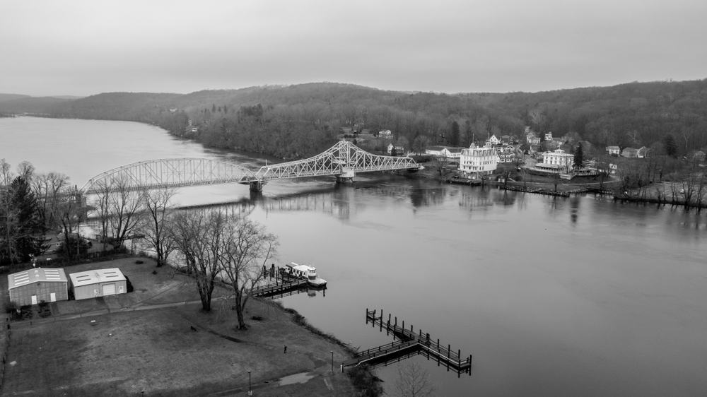 An image in greyscale of a bridge over a river, with a classic white building, an opera house, on the distant shore
